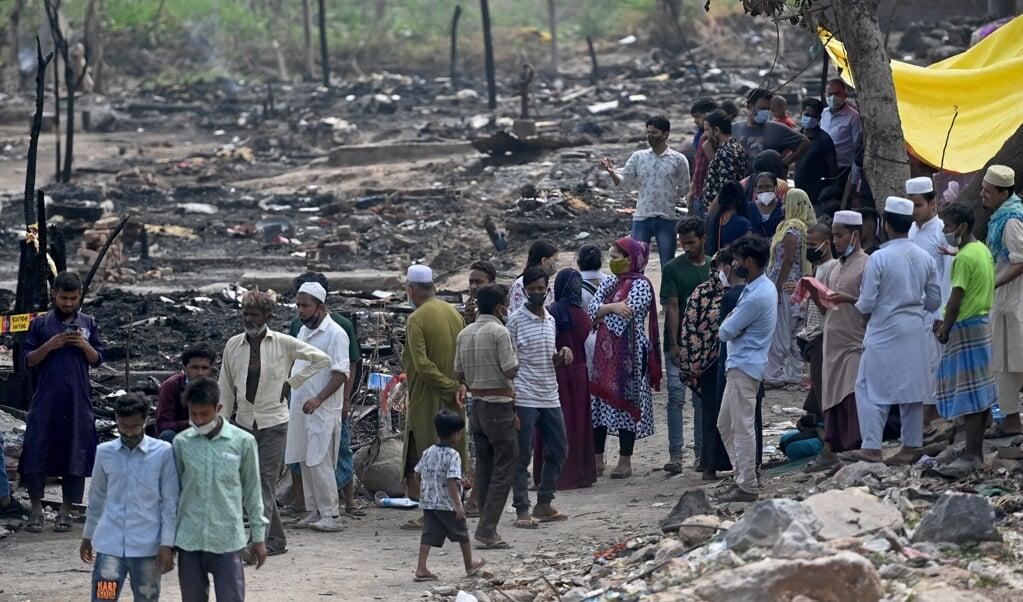 Rohingya-vluchtelingen verzamelen zich bij de verkoolde resten van hun kamp in New Delhi waar een brand uitbrak.  (beeld afp / Money Sharma)