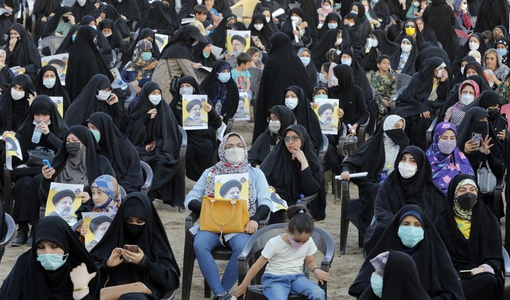 Iraanse vrouwen voeren campagne voor de ultraconservatieve presidentskandidaat Ebrahim Raisi.   (beeld afp)
