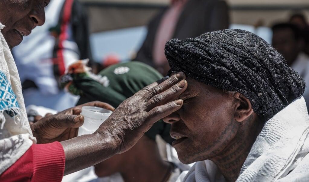 Een vrouw in Ethiopië krijgt met olie een kruis op haar voorhoofd getekend tijdens de herdenking van een vliegramp, maart 2020. Het christelijke kruissymbool illustreert een fundamentele omkering van macht, wereldwijd.  (beeld afp / Eduardo Soteras)