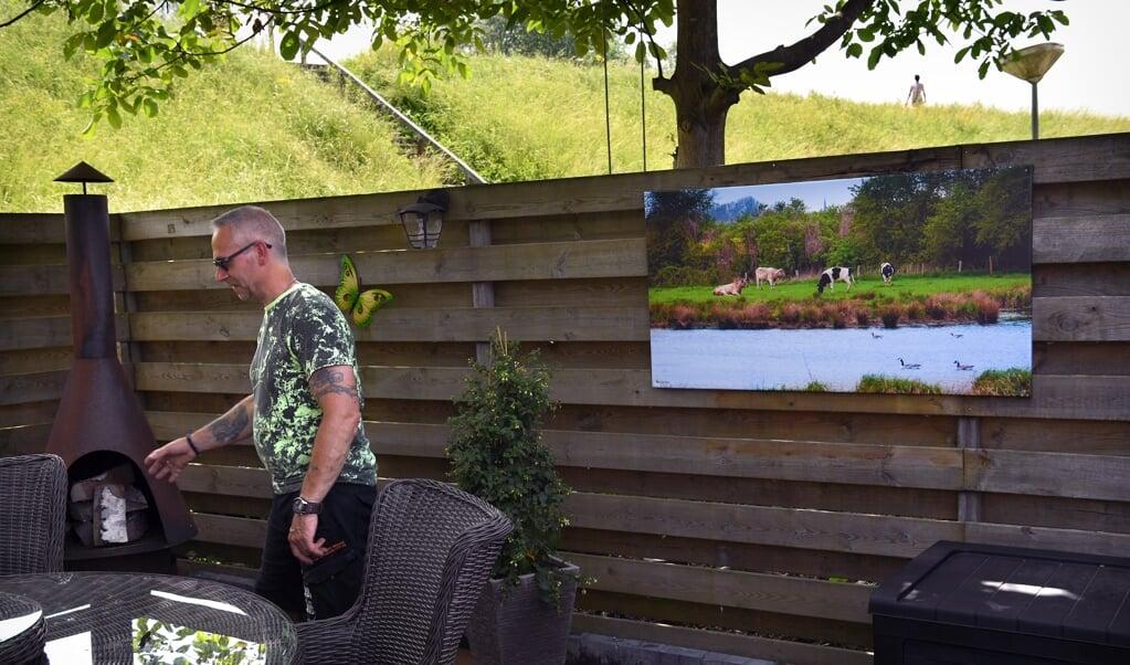 De achtertuin van een bewoner in Heesselt, met op de achtergrond de Waaldijk.   (beeld Marcel van den Bergh)
