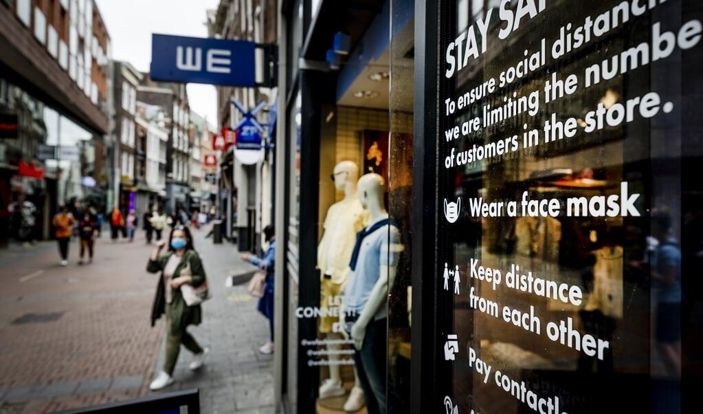 Een winkelruit in Amsterdam herinnert passanten aan de coronamaatregelen.  (beeld anp / Remko de Waal)