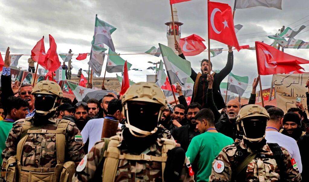 Door Turkije gesteunde Syrische radicaal-islamitische militieleden hijsen hun vlag en die van Turkije in Afrin. Sinds 2018 maakt Turkije samen met de milities de dienst uit in de Syrische regio.  (beeld afp / Aaref Watad)