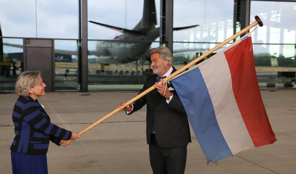 Minister van Defensie Ank Bijleveld draagt een van de missievlaggen over aan directeur Paul van Vlijmen van het Nationaal Militair Museum.  (beeld Riekelt Pasterkamp)