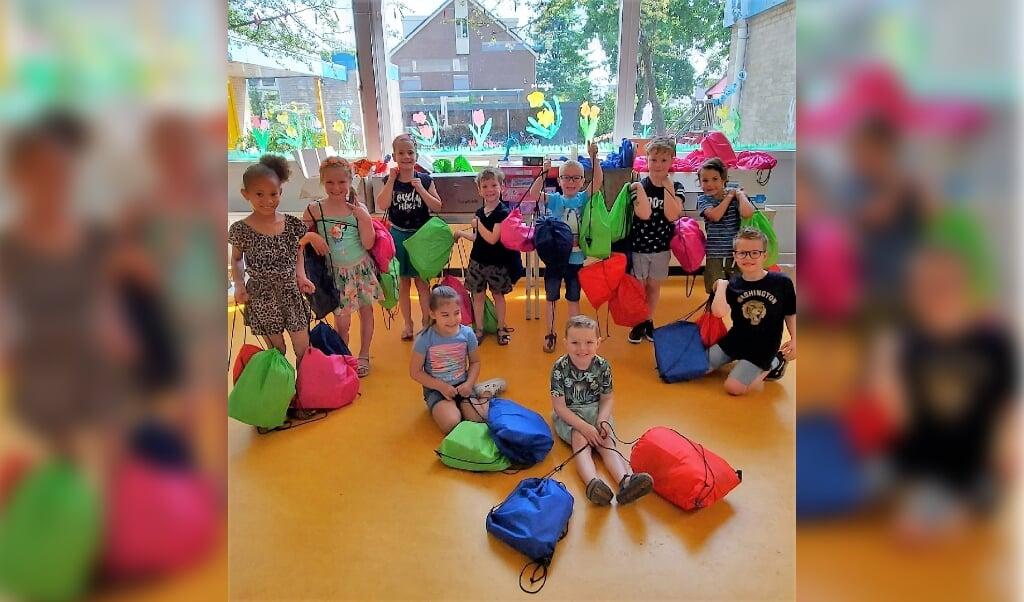 Leerlingen van de Koepelschool in Ede vulden tasjes voor vluchtelingenkinderen.  (beeld koepelschool)
