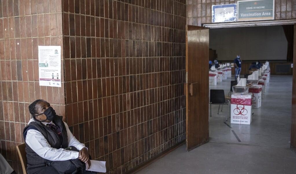 Een Zuid-Afrikaanse vrouw wacht in het ziekenhuis in Germinston op haar beurt om een vaccinatie te krijgen.   (beeld afp / Michele Spatari )