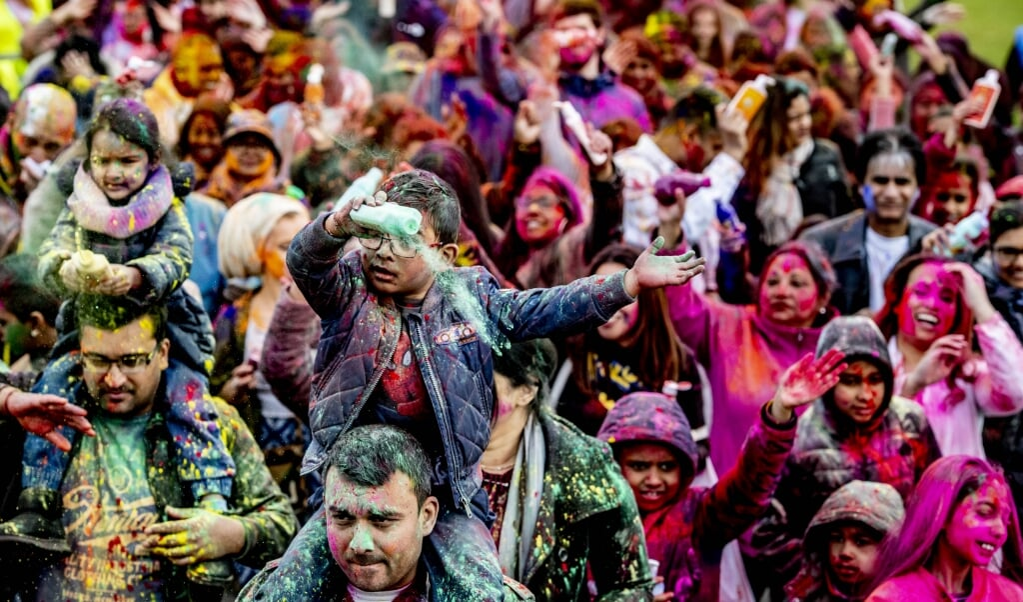 Hindoestanen besprenkelen elkaar met kleurrijk poeder tijdens de viering van het Holifeest in Den Haag. 'In de bundel blijkt dat zij zich niet gekend en erkend voelen binnen de geestelijke gezondheidszorg.'  (beeld anp / Robin Utrecht)