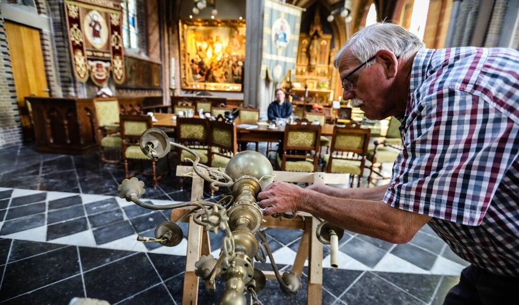In de Sint Laurentiuskerk is Kees Pater bezig een oude kroonluchter op te kalefateren.  (beeld Maarten Boersema)