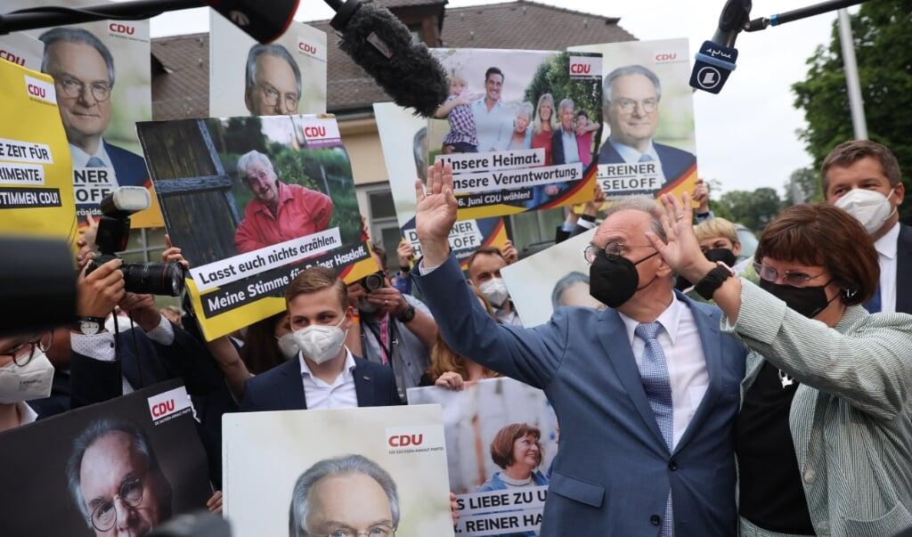 CDU-regeringsleider Reiner Haseloff en zijn vrouw Gabriele Haseloff zwaaien naar publiek en partijleden in na de winst in Saksen-Anhalt.  (beeld afp / Ronny Hartmann)