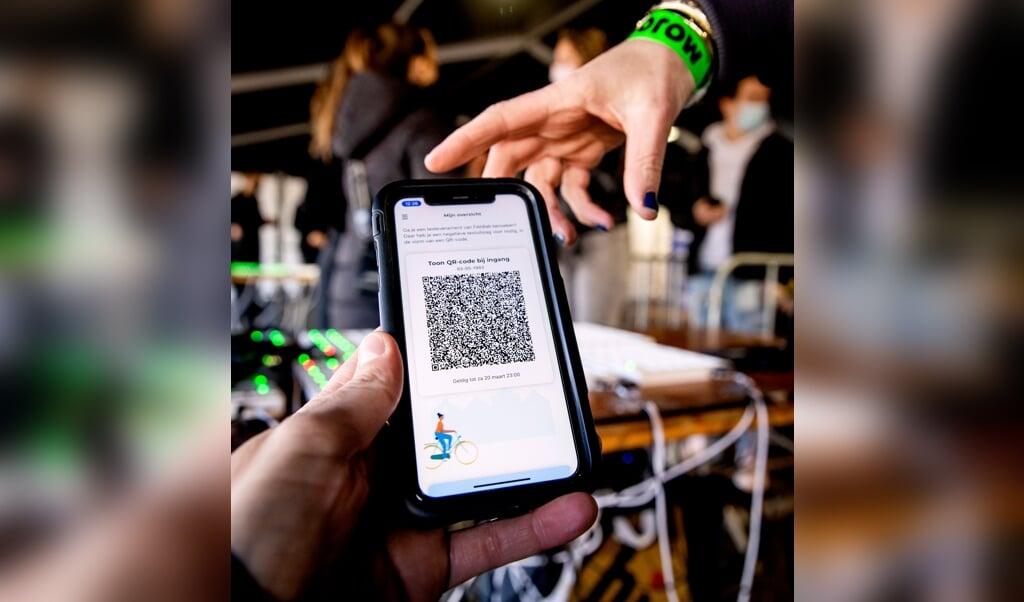 Bezoekers van een dancefestival op het evenemententerrein van Walibi Holland laten bij binnenkomst hun QR-code scannen, om te kijken of er sprake is van een negatieve test.   (beeld anp / Koen van Weel)