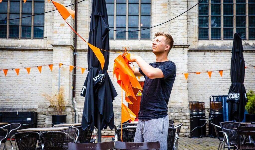 Een caféhouder in de binnenstad van Breda ruimt de EK-versiering op.   (beeld hollandse hoogte / Jeffrey Groeneweg)