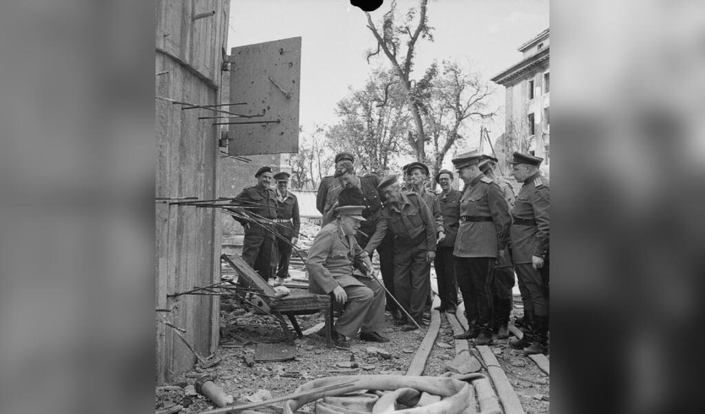 Winston Churchill zit op een tuinstoel bij de Führerbunker.  (beeld Imperial War Museums (IWM) Londen / wikimedia)