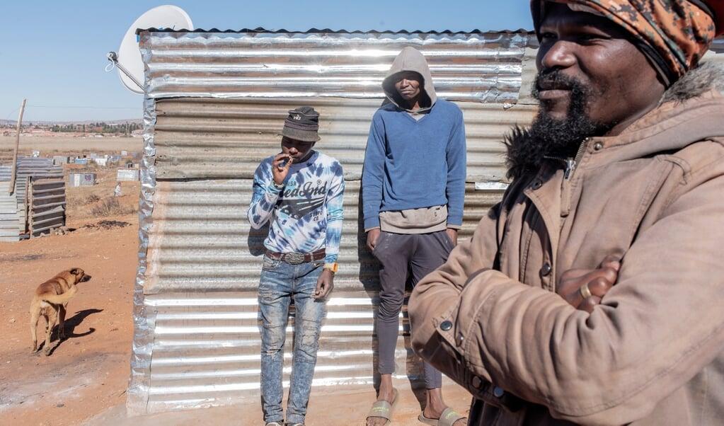 Bongani Ngubane (rechts) in de illegale nederzetting die hij oprichtte bij Johannesburg.  (beeld Luca Sola)