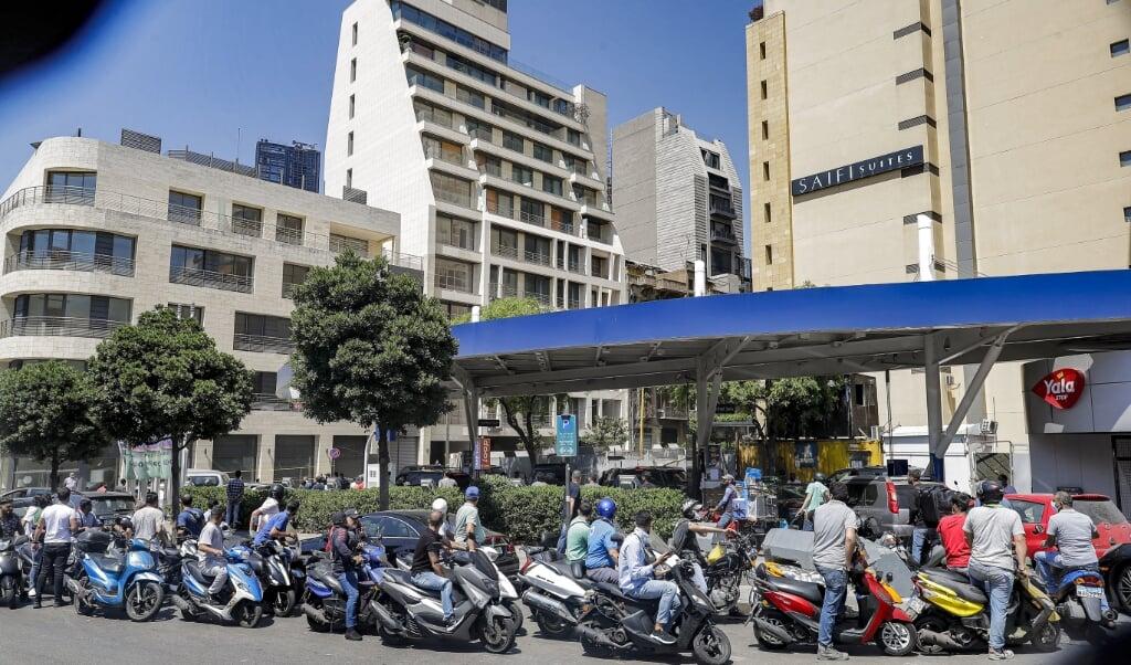Een lange rij wachtenden voor een benzinestation in Beiroet.  (beeld afp / Joseph Eid)