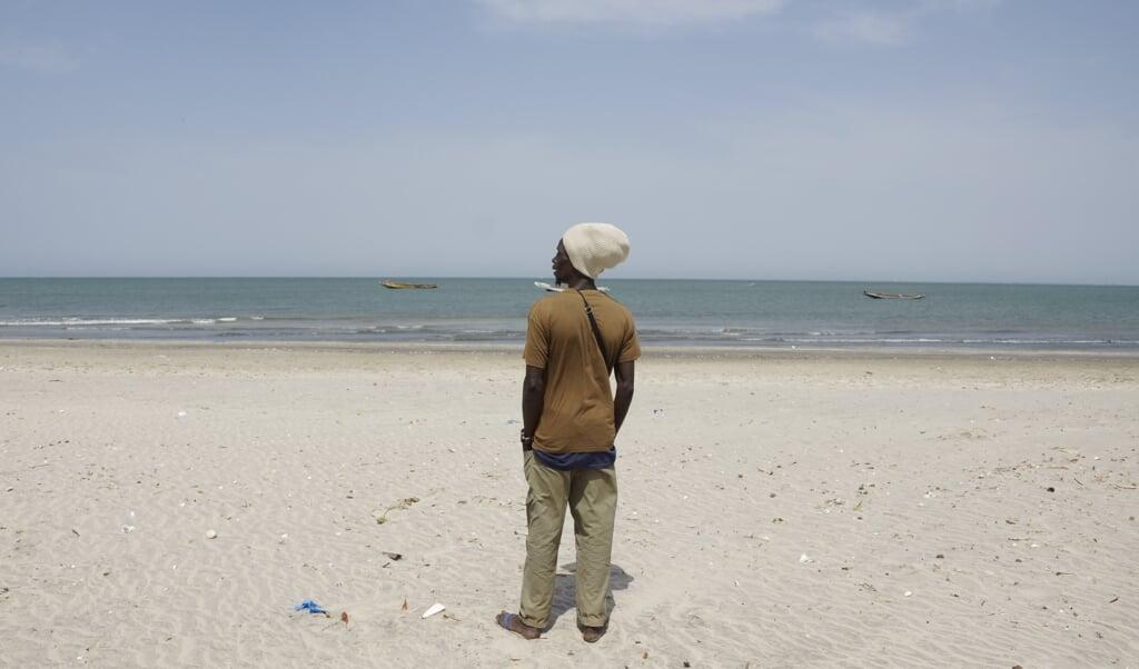 Een potentiële migrant op het strand van Bakau in Gambia. Vanaf de Gambiaanse kust is het hemelsbreed 1700 kilometer naar Gran Canaria.  (beeld Lex Rietman)