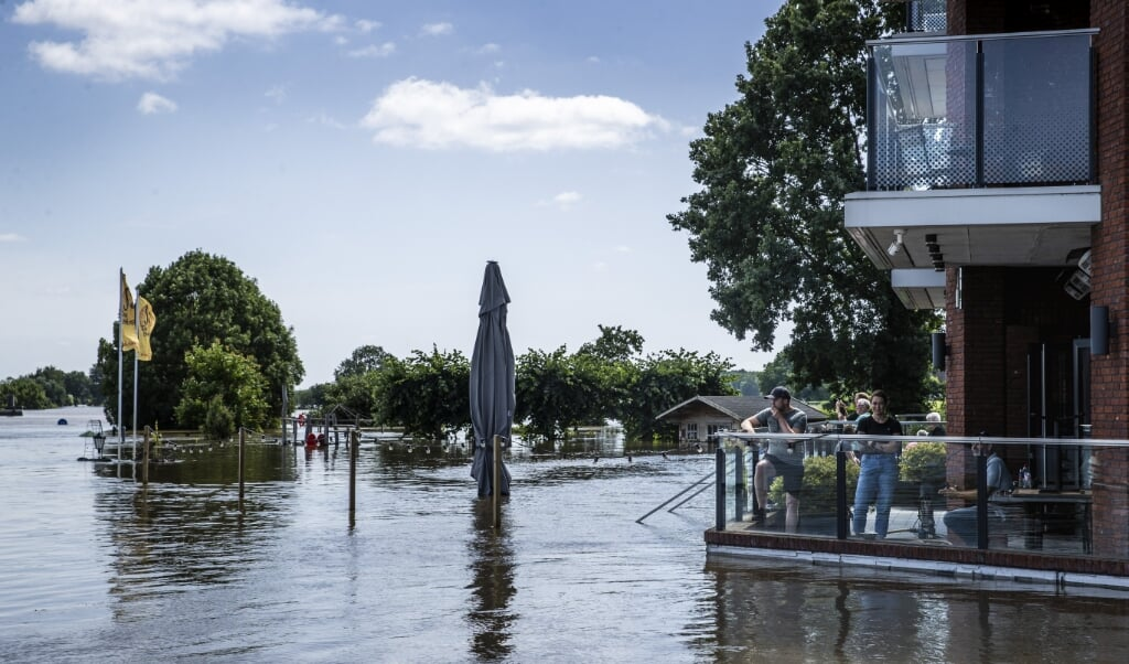 Bewoners van Broekhuizen kijken vanaf een terras naar het hoge water in de Maas. Limburg is getroffen door overstromingen.  (beeld anp / Vincent Jannink)