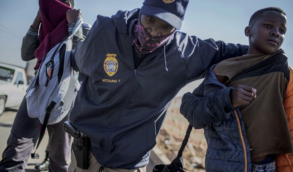 De plunderaars zijn meestal arme jongeren, zoals deze jongen die is opgepakt bij de plundering van een winkelcentrum in Soweto, Johannesburg. Van de Zuid-Afrikaanse jeugd is 63,3 procent werkloos.   (beeld afp / Luca Sola)