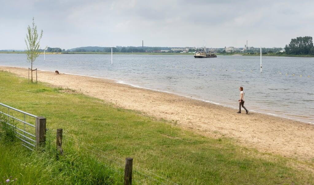 Breed en uitgestrekt kun je het bepaald niet noemen, dit strandje. Maar er is toch alle ruimte. Aan de overkant de Parencofabriek bij Renkum.  (beeld Niek Stam)