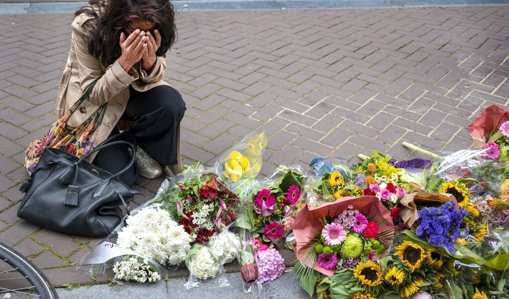 Mensen laten bloemen, kaarsjes en steunbetuigingen aan Peter R. de Vries achter in de Lange Leidsedwarsstraat in het centrum van Amsterdam.  (beeld anp / Evert Elzinga)