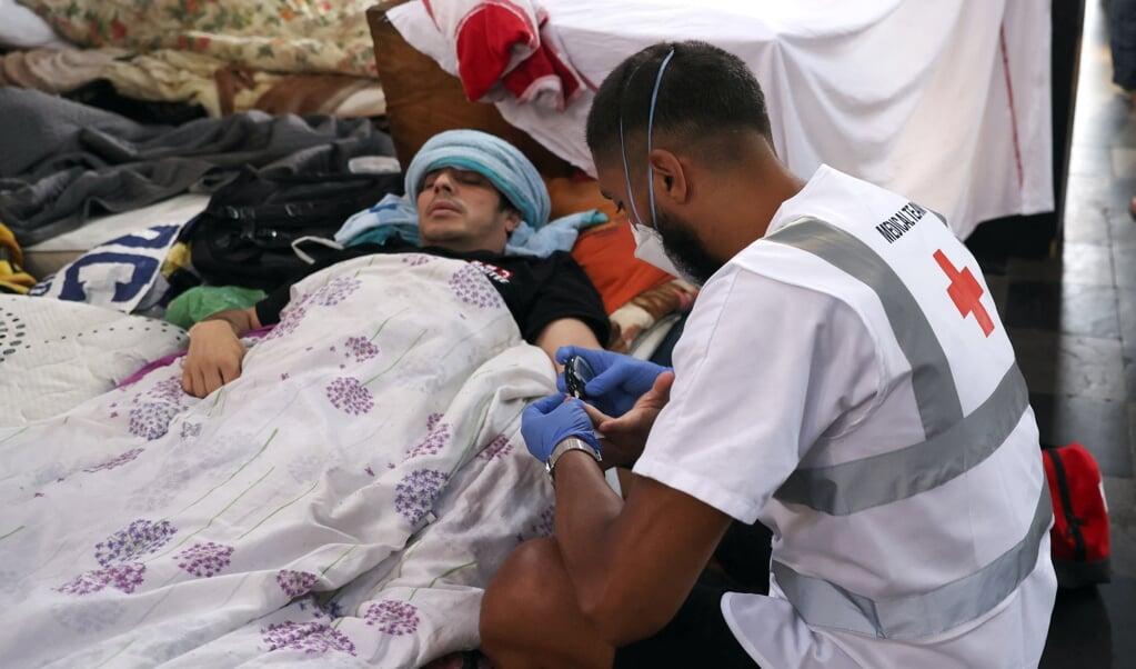 Een van de hongerstakers in de Begijnhofkerk in Brussel krijgt medische hulp.  (beeld afp)