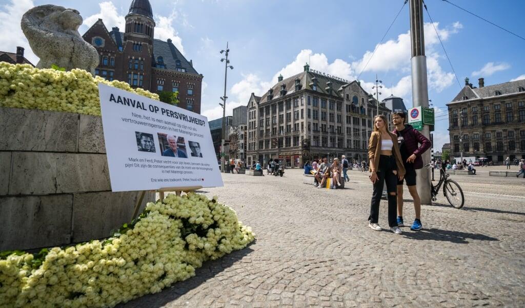 Witte rozen bij het Nationaal Monument op de Dam als steunbetuiging voor Peter R. de Vries.   (beeld anp / Jeroen Jumelet)