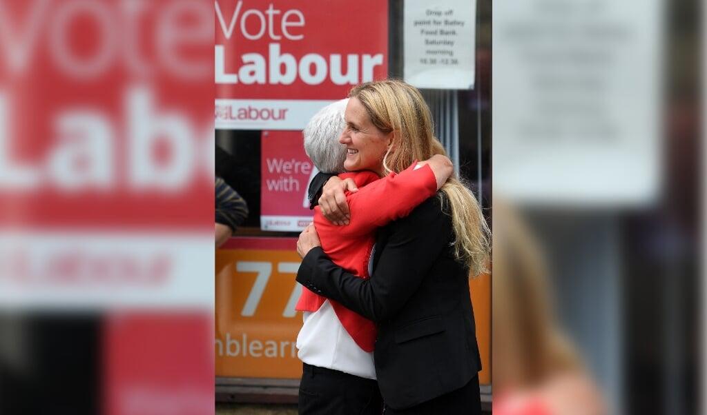 Kim Leadbeater knuffelt haar moeder Jean nadat bekend is geworden dat zij haar opponent in het kiesdistrict Batley and Spen had verslagen.  (beeld afp / Oli Scarff)