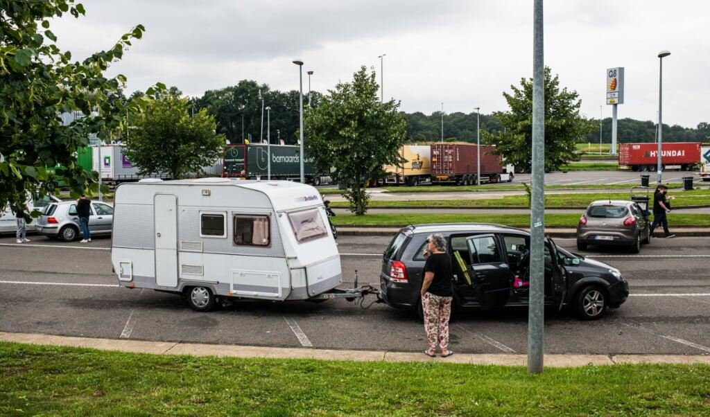 Nederlandse vakantiegangers bij een Belgische benzinepomp.  (beeld anp / Jonas Roosens)