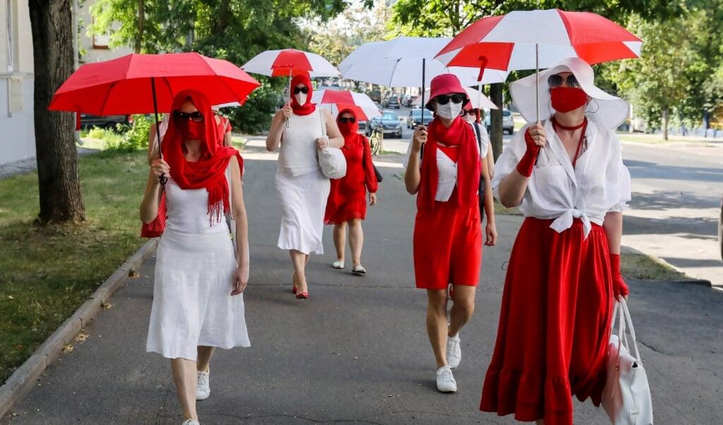 Belarussische vrouwen die kleding dragen en paraplu's vasthouden in de kleuren van een Belarussische protestvlag, marcheren tijdens een demonstratie tegen de regering en de Belarussische president Loekasjenko in Minsk, Belarus, 18 juli 2021. Ondanks martelingen, arrestaties en strafzaken voor het hebben en tonen van symbolen in nationale kleuren, blijven Belarussische vrouwen protesteren. Volgens de deelnemers roept de wandeling op tot empathie en solidariteit met de slachtoffers van de aanhoudende repressie.  (beeld epa)