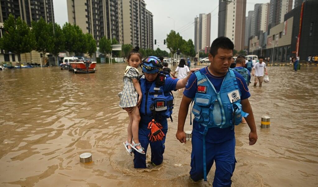 Reddingswerkers helpen een meisje in de ondergelopen straten van Zhengzhou. Hulpvragen en klachten van inwoners worden van sociale media verwijderd door de Chinese overheid.  (beeld afp / Noel Celis)