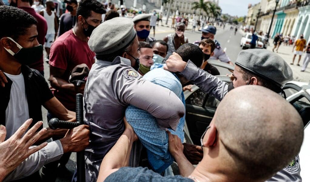 Een man wordt gearresteerd in de Cubaanse hoofdstad Havana, tijdens een historisch volksprotest.   (beeld afp / Adalberto Roque)