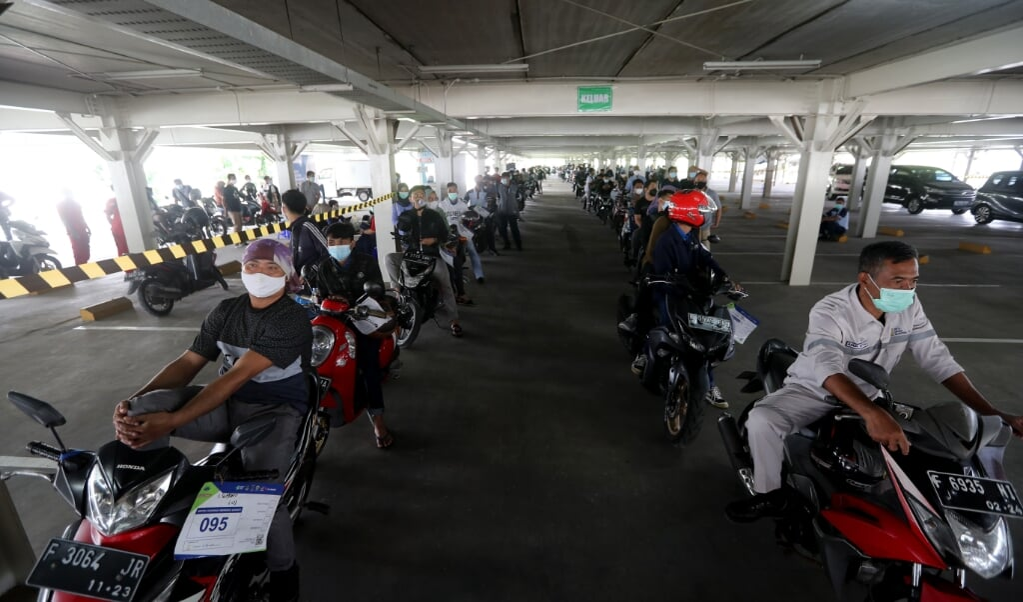 Motorrijders staan op een parkeerplaats bij een ziekenhuis in Jakarta in de rij voor een vaccinatie. In de stad sterven mensen op straat aan corona.  (beeld epa / Bagus Indahono)