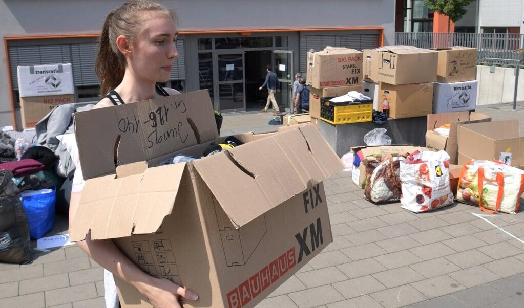 Scholieren helpen als vrijwilliger bij het Ville Gymnasium school in Erftstadt.  (beeld afp / Sebastien Bozon)