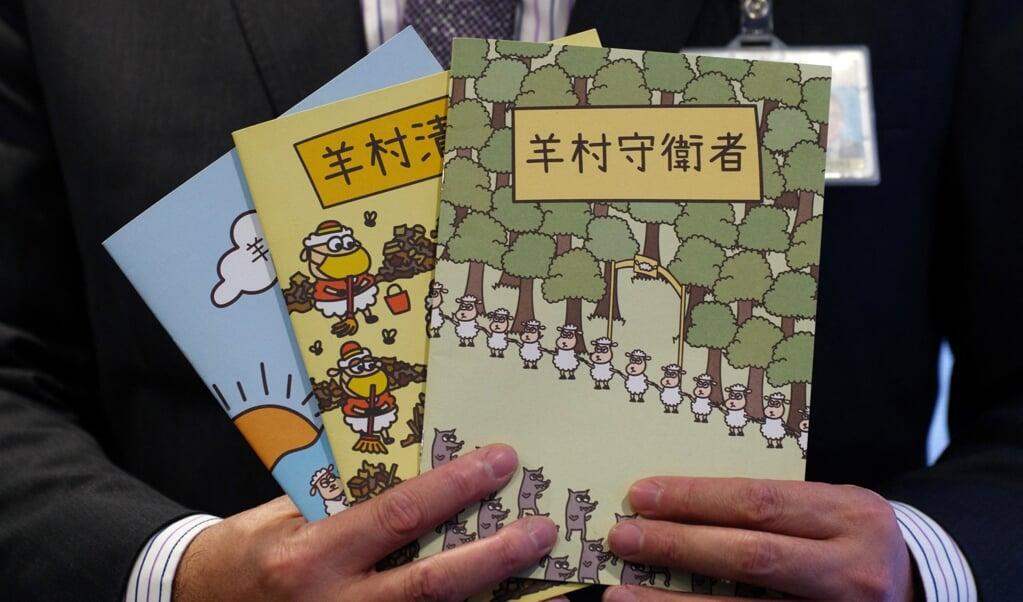 Hongkongs veiligheidschef Steve Li toont de gewraakte kinderboeken.  (beeld afp / Daniel Suen)