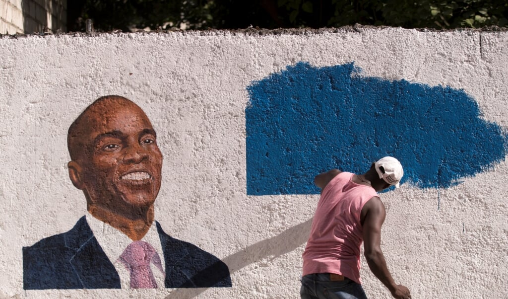 2021-07-19 22:33:03 epa09353947 A man paints a mural in tribute to the assassinated President Jovenel Moise, in Port-au-Prince, Haiti, 19 July 2021. Haiti designate Prime Minister Ariel Henry is to take over from interim Prime Minister Claude Joseph on 20 July. Slain President Jovenel Moise had appointed Ariel Henry to the position, but he had not officially taken office before the assassination. Since then, Claude Joseph has led the country as interim Prime Minister and on 20 July he will hand over the position to Henry, thus ending a fight between the two and the President of the Senate, Joseph Lambert, the third contender for Prime Minister.  EPA/Orlando Barría  (beeld Epa/orlando Barrãa)