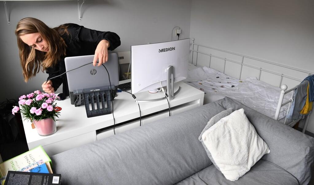 Leonie Schenkel plugt de laptop in in haar 'kantoor' van dertien vierkante meter.   (beeld Marcel van den Bergh)