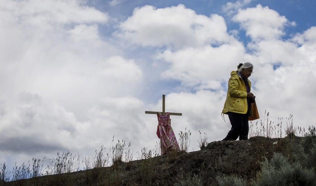 Een kruis met een meisjesjurk herinnert bij het voormalige internaat in Kamloops aan de 215 anonieme kinderen die er op het grondgebied begraven liggen.   (beeld afp / Cole Burston)