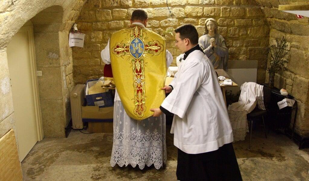 Een rooms-katholieke priester viert de tridentijnse mis.   (beeld afp / Thomas Coex)
