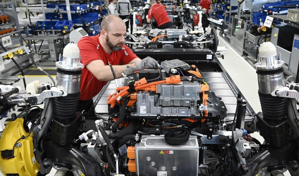 Een medewerker van Porsche werkt aan de productie van een electrische Taycan. De bouw en het onderhoud van elektrische auto's vraagt hoger opgeleid personeel.  (beeld afp / Thomas Kienzle)