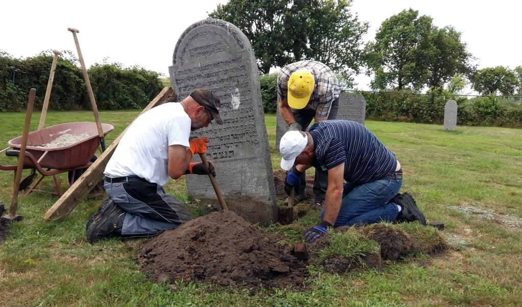Vrijwilligers helpen met de renovatie van een Joodse begraafplaats.  (beeld stichting boete en verzoening)