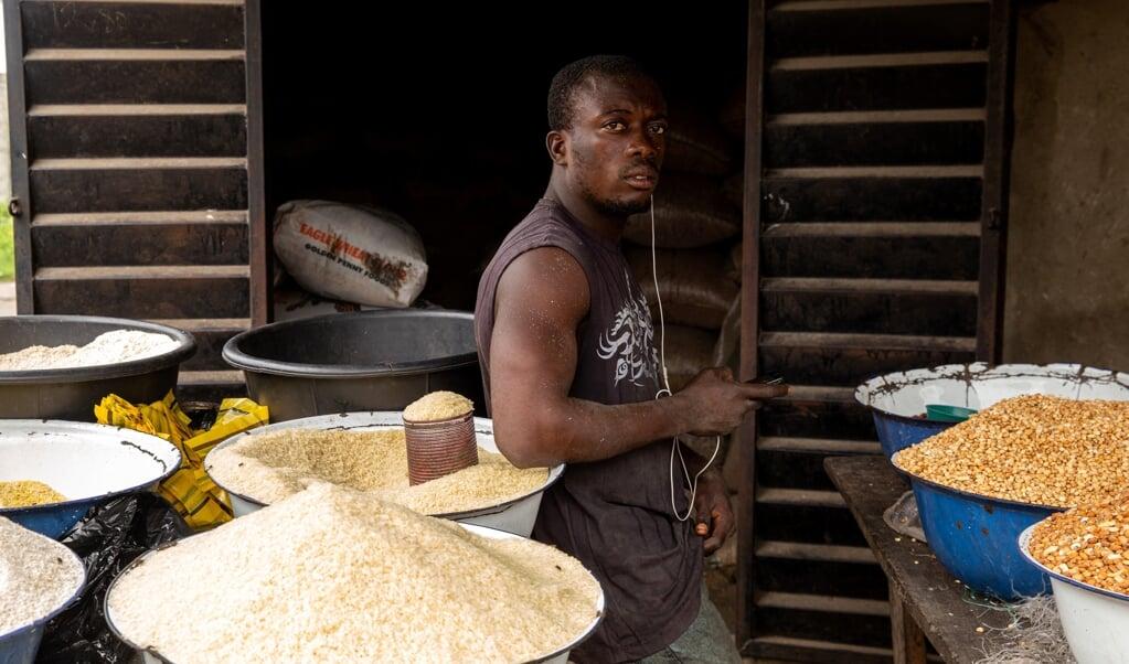 Een Nigeriaan poseert in zijn rijstwinkel in Badagry, bij Lagos, september 2019. 'Toch kiest Verre Naasten ervoor om zelfbewuste, krachtige broers en zussen uit bijvoorbeeld Afrika en Azië te portretteren.'  (beeld afp / Benson Ibeabuchi)