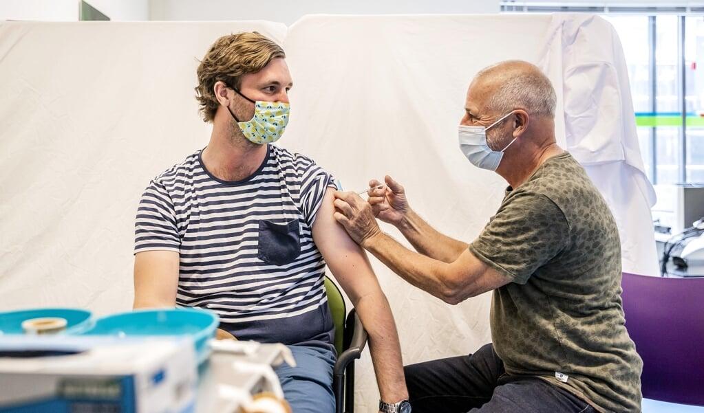 Een bewoner uit een Haagse wijk laat zich vaccineren in een gezondheidscentrum.  (beeld anp / Remko de Waal)