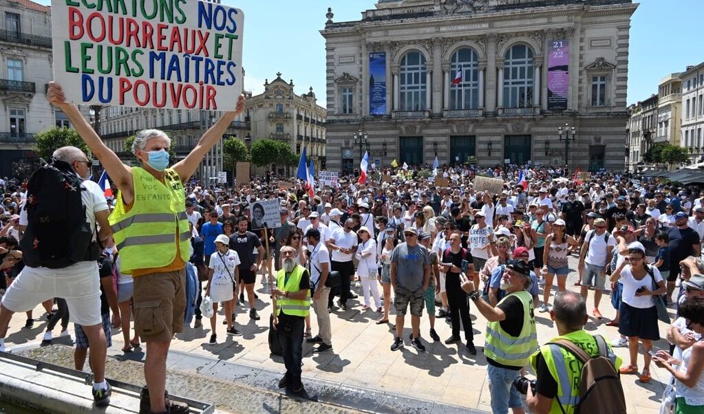 'Laten we onze beulen en hun machthebbers aan de kant zetten', staat er op dit bord, een leus uit de Franse revolutie. Het protest in Montpellier is tegen verplichte vaccinatie voor bepaalde werknemers en de verplichte gezondheidspas.  (beeld afp / Pascal Guyot)