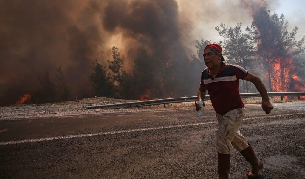 Een man vlucht weg voor de bosbranden in de Turkse stad Marmaris.  (beeld epa / Erdem Sahin)