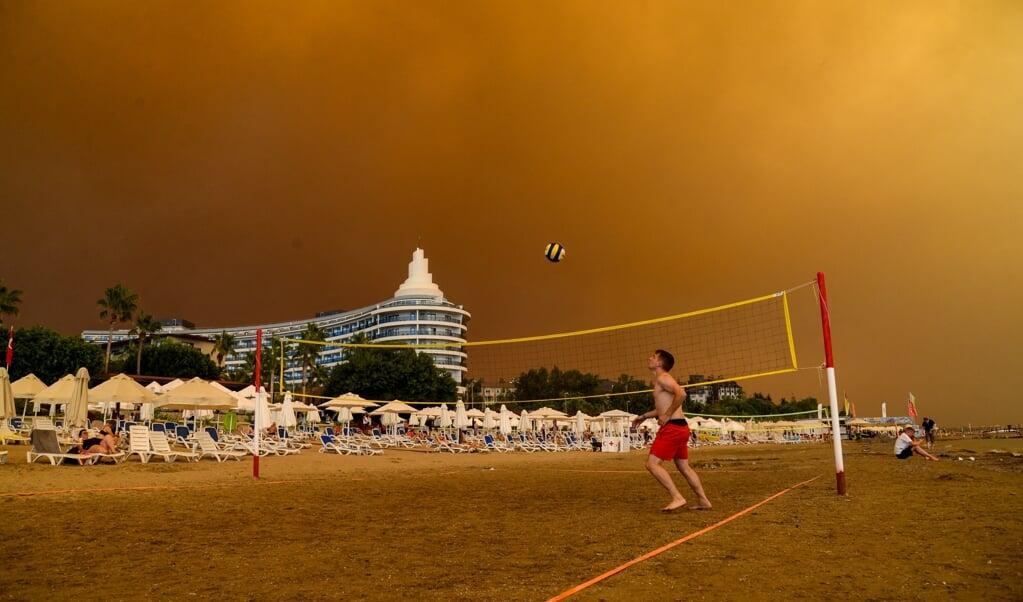 Rookwolken vullen de lucht boven een hotelcomplex en het strand van de Turkse badplaats Manavgat. Vanwege de hittegolf in de regio ontstaan honderden bosbranden.   (beeld afp / Ilyas Akengin)