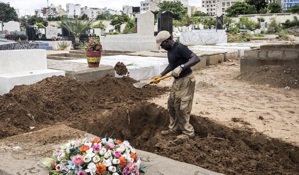 Een man graaft een nieuw graf op een begraafplaats in Dakar. Met een derde golf van COVID-19 die Senegal treft, zien begraafplaatsen een verdubbeling van het aantal begrafenissen.  (beeld afp / John Wessels)