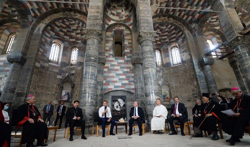 De Franse president Macron (midden  links) in kerk van de dominicanen in Mosul, de Notre-Dame de l'Heure. Deze kerk werd vier jaar geleden door ISIS verwoest en is hersteld met financiële steun van de Verenigde Naties.  (beeld afp / Zaid Al-obeidi)