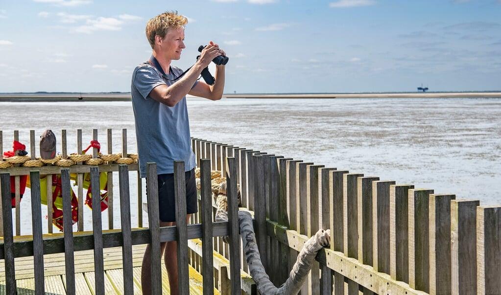 Met behulp van een verrekijker houdt vrijwilliger Wout Bakker de vogelstand op Engelsmanplaat in de gaten.  (beeld Guus Dubbelman)