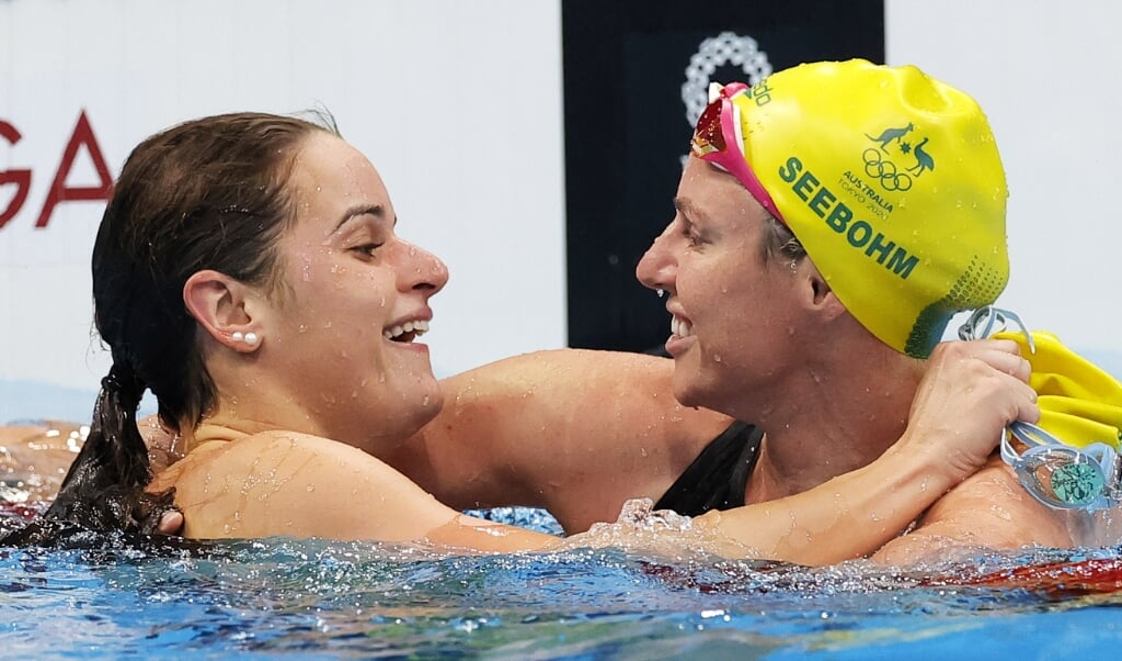 Een overwinning die wordt gedeeld: de Australische zwemster Kaylee McKeown (l.) krijgt de felicitaties van haar teammaat Emily Seebohm na het winnen van de honderd meter rugslag op de Olympische Spelen in Tokio, die zondag werden afgesloten.  (beeld epa / Valdrin Xhemaj)