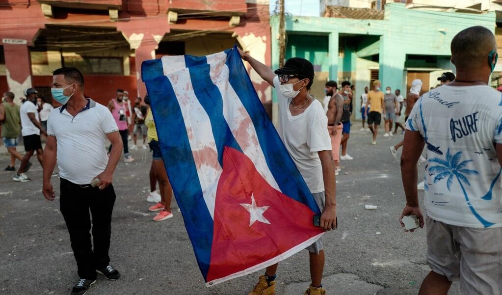 Een demonstrant wappert met de Cubaanse vlag tijdens de protesten van 11 juli.  (beeld Thousands of Cubans Took Part in Rare Protests Sunday Against the Communist Government, Marching Through a Town Chanting 'down With the Dictatorship' and 'we Want Liberty.' Adalberto Roque / afp)