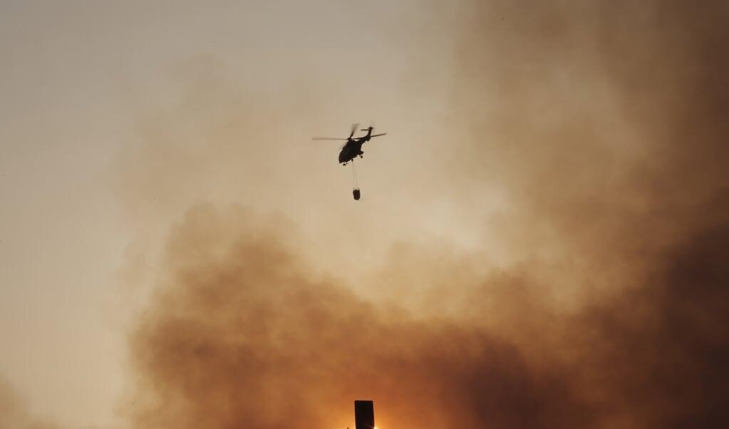 Een blushelikopter vliegt - terwijl de zon ondergaat - achter een kruis dat bovenop een klooster staat in Kryoneri, ten noordoosten van de Griekse hoofdstad Athene. Meer brandweerlieden en ondersteuning vanuit de lucht zijn toegevoegd aan het gevecht tegen de heropleving van de bosbranden in het gebied. In totaal worden negen helikopters en vier vliegtuigen ingezet bij het bestrijden van het vuur vanuit de lucht. De politie heeft het verkeer in de omgeving stilgelegd. In het Tatoi-bos staat ook het voormalige zomerpaleis van de vroegere koninklijke familie van Griekenland. Het opnieuw oplaaien van het vuur, vanwege de wind en de extreem hoge temperaturen, heeft ook geleid tot nieuwe evacuaties in het gebied rondom Athene.  (beeld epa / Kostas Tsironis)