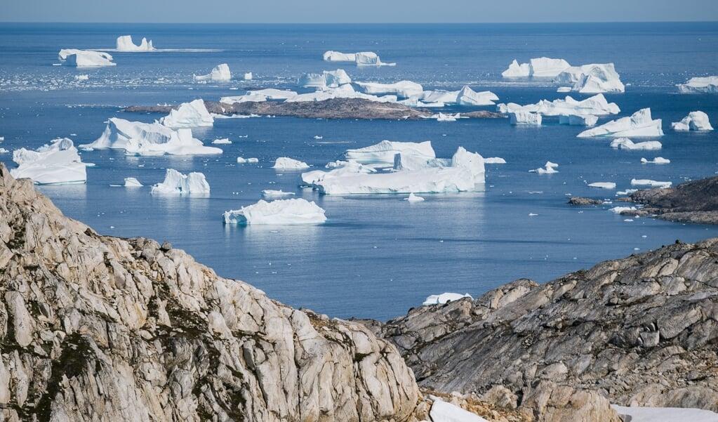 IJsbergen drijven  langs de oostelijke kust van Groenland bij Kulusuk. De temperatuur van de aarde is nog nooit zo snel gestegen als nu.  (beeld afp / Jonathan Nackstrand)